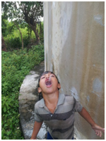Honduran child enjoys a drink of clean, chlorinated water made possible by Engineers without Borders, Water for People, and others