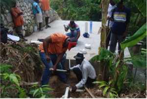 Workers in Haiti install chlorinator equipment to disinfect a community water supply a measure that will help prevent waterborne illness